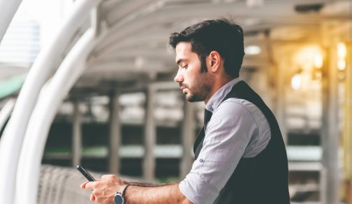 Businessmen are standing on the train station, they are stressed While he is using the mobile phones To view performance data, to business concept.