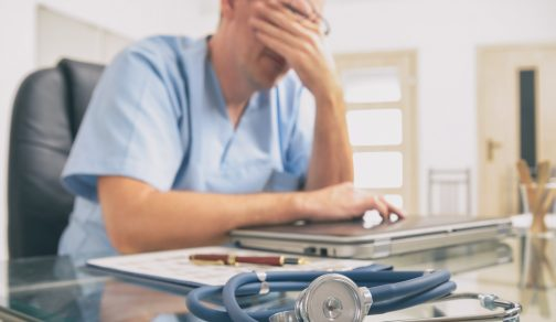 Overworked doctor sitting in his office. Focus on stethoscope in foreground