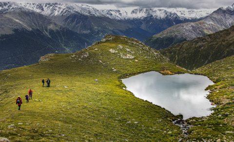 mountain-hikers-go-around-a-mountain-lake